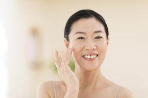 頬に片手を添えて笑う女性の写真素材 [FYI02969012]