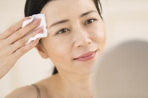 頬にコットンをあてスキンケアをする女性の写真素材 [FYI02969014]