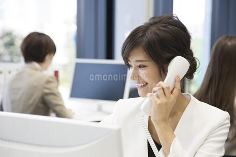 パソコンの前で電話をするビジネス女性の写真素材 [FYI02969019]