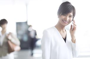 スマートフォンで通話するビジネス女性の写真素材 [FYI02969021]