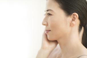 頬に片手を添える女性の横顔の写真素材 [FYI02969022]