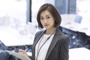 資料を持ちカメラ目線のビジネス女性の写真素材 [FYI02969024]