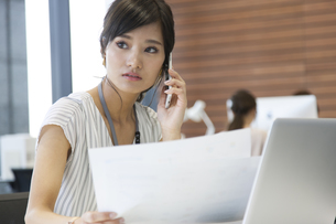 横を向いて電話をするビジネス女性の写真素材 [FYI02969034]