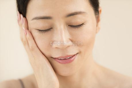 頬に片手を添えて目を瞑り微笑む女性の写真素材 [FYI02969037]