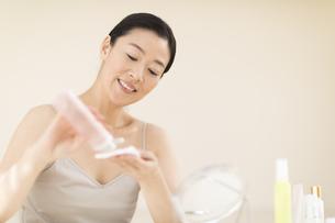 コットンに化粧水を湿らす女性の手の写真素材 [FYI02969042]