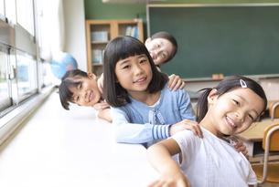 教室の窓際で重なって笑う女の子たちの写真素材 [FYI02969043]