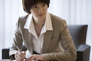 手帳を広げて1点を見るビジネス女性の写真素材 [FYI02969047]