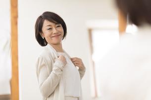 鏡の前で洋服を合わせる女性の写真素材 [FYI02969051]