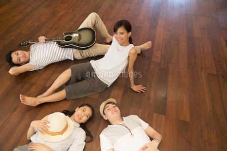 床に寝転んでくつろぐ男女の写真素材 [FYI02969053]