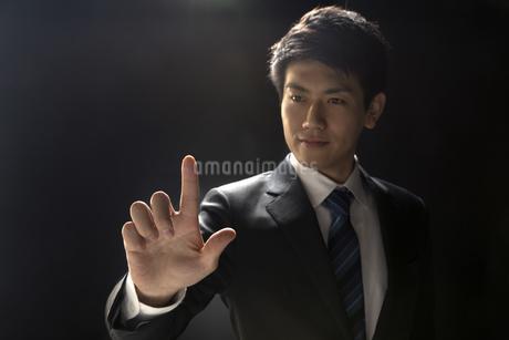 指を指すポーズをとるビジネス男性の写真素材 [FYI02969055]