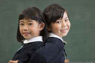 黒板の前で背中を合わせる小学生の女の子3人の写真素材 [FYI02969056]