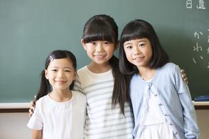 黒板の前で肩を組んで笑う女の子3人の写真素材 [FYI02969058]
