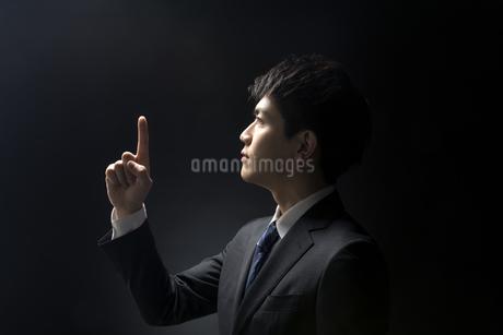 指を指すポーズをとるビジネス男性の横顔の写真素材 [FYI02969059]