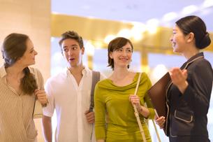 コンシェルジュの案内を受ける男女3人の外国人の写真素材 [FYI02969065]
