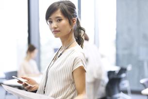 スマホを持ち横を向くビジネス女性の写真素材 [FYI02969068]