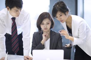 ノートパソコンを見る3人のビジネス男女の写真素材 [FYI02969072]