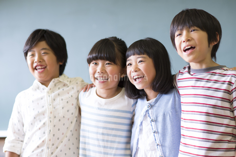 黒板の前で肩を組んで笑う子供たちの写真素材 [FYI02969076]