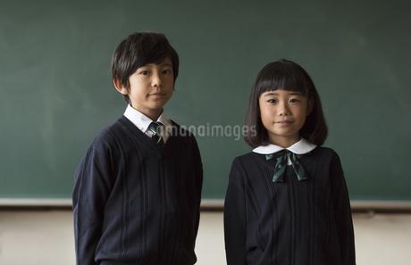 黒板の前に立って微笑む小学生の男女の写真素材 [FYI02969083]