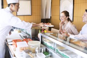 寿司を受け取る外国人の男女の写真素材 [FYI02969087]
