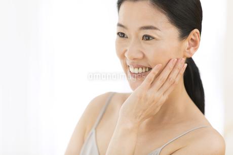 頬に片手を添えて微笑む女性の写真素材 [FYI02969088]