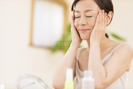 鏡の前でスキンケアをする女性の写真素材 [FYI02969091]