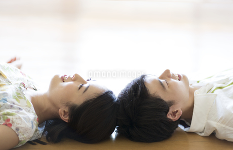 寝転がり頭をくっつける男女の写真素材 [FYI02969096]