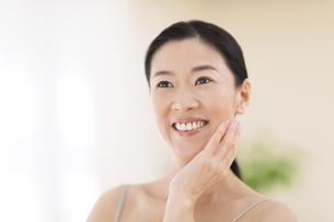 頬に片手を添えて微笑む女性の写真素材 [FYI02969098]