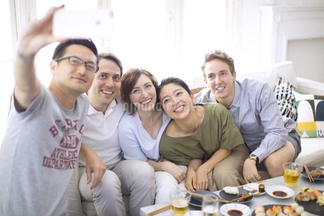ホームパーティーで記念撮影をする外国人と日本人の写真素材 [FYI02969104]