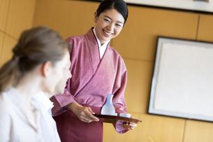 外国人に日本酒を出す女性店員の写真素材 [FYI02969105]