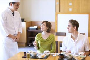 板前と話しながら日本料理を食べる外国人の男女の写真素材 [FYI02969108]