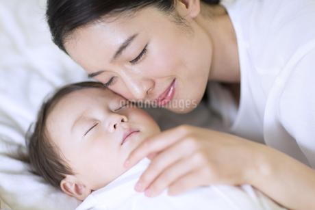 眠っている赤ちゃんに頬を寄せる母親の写真素材 [FYI02969109]
