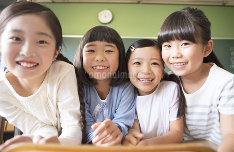 教室で肩を並べて笑う女の子4人の写真素材 [FYI02969110]