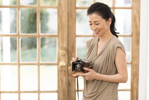 カメラを手に持って微笑む女性の写真素材 [FYI02969113]