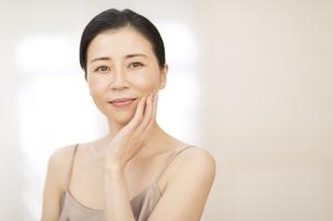 頬に片手を添えて微笑む女性の写真素材 [FYI02969117]