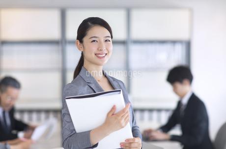 ファイルを持ちカメラ目線のビジネス女性の写真素材 [FYI02969120]