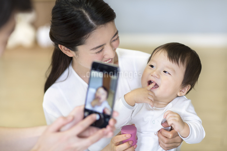 母親に抱かれて写真を撮られる赤ちゃんの写真素材 [FYI02969132]