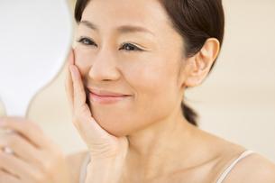 手鏡を見て微笑む女性の写真素材 [FYI02969133]