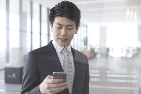 スマートフォンを操作するビジネス男性の写真素材 [FYI02969135]