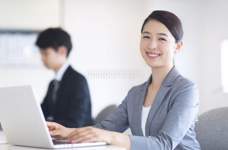 パソコンの前でカメラ目線のビジネス女性の写真素材 [FYI02969139]