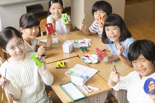 色を塗った作品を見せる子供たちの写真素材 [FYI02969142]