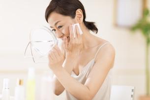 頬にコットンをあてスキンケアをする女性の写真素材 [FYI02969146]