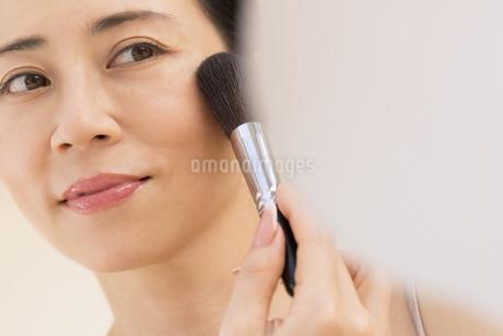 チークブラシを顔にあてる女性の写真素材 [FYI02969147]