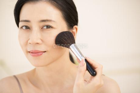 チークブラシを顔にあてる女性の写真素材 [FYI02969148]