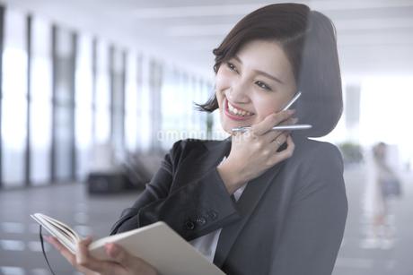 手帳を開きスマートフォンで通話するビジネス女性の写真素材 [FYI02969149]