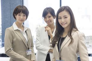 オフィスでカメラ目線で立つ3人のビジネス女性の写真素材 [FYI02969161]