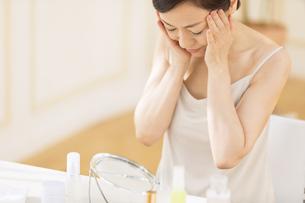 鏡の前でスキンケアをする女性の写真素材 [FYI02969169]