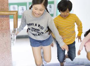 学校の階段を駆ける女の子と男の子の写真素材 [FYI02969170]