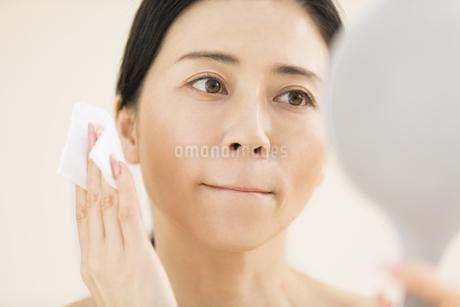 頬にコットンをあてスキンケアをする女性の写真素材 [FYI02969172]
