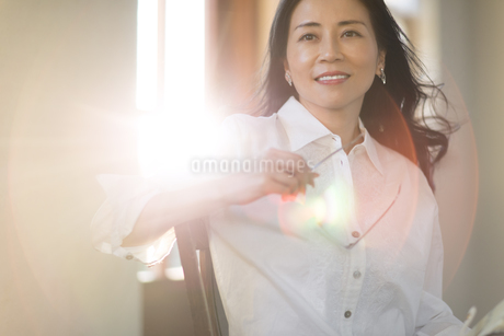 眼鏡を手に持って遠くを見つめる女性の写真素材 [FYI02969173]