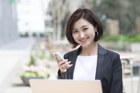 カメラ目線でスマートフォンを持つビジネス女性の写真素材 [FYI02969184]